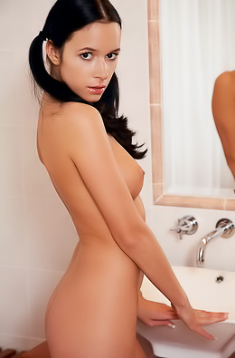 Naked cutie enjoys her hot body in a big mirror.