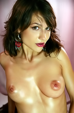 Naked babe oils her natural boobs.